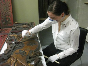 Michelle Derrick cleaning a Chinese temple carving